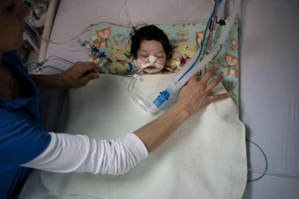 A nurse places a blanket over an infant