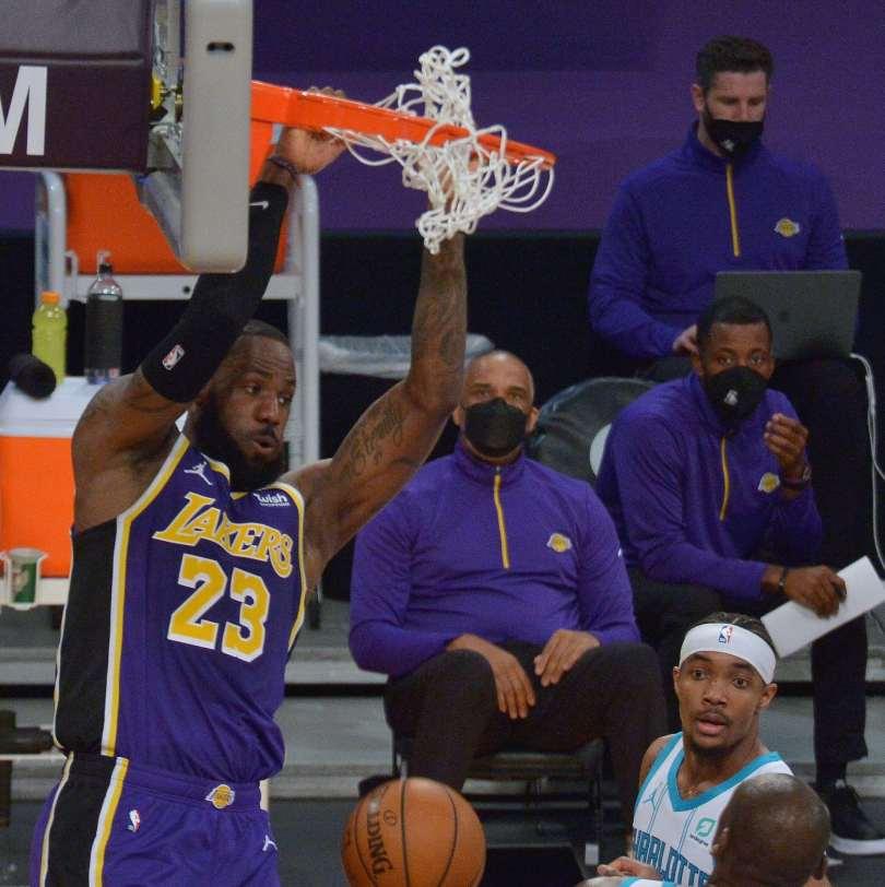 Basketball player hangs off the basket.