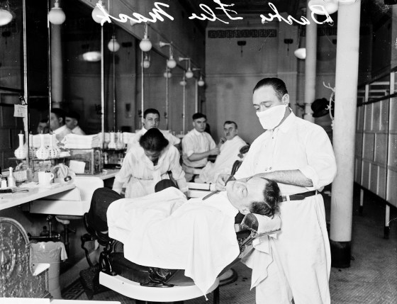 a masked barber shakes a customer