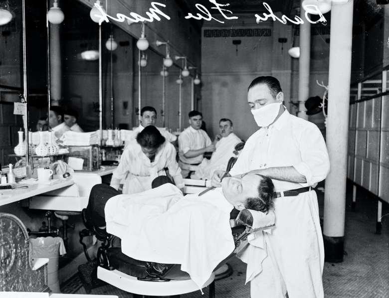masked barber shaves a customer