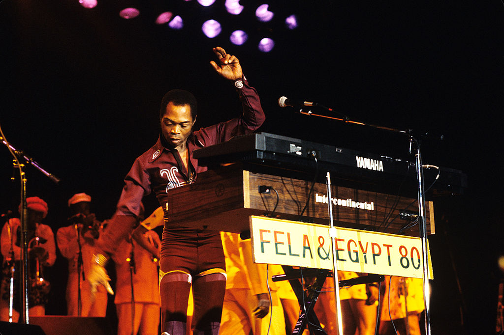 A man standing on stage in partly behind keyboards.
