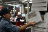 An inspector checks a copy of the Washington Post for quality control