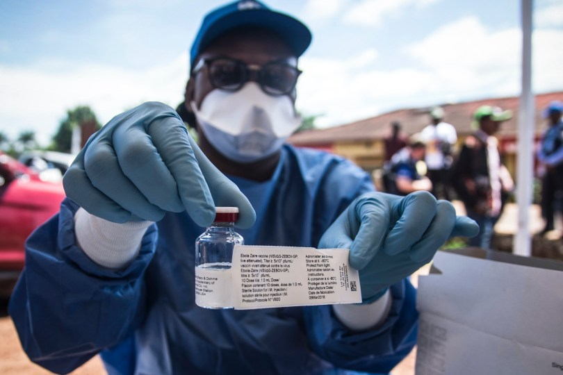 A worker from the World Health Organization (WHO) holds up a vaccination as he prepares to administer it during the launch of an experimental Ebola vaccine in Mbandaka, north-western Democratic Republic of the Congo.
