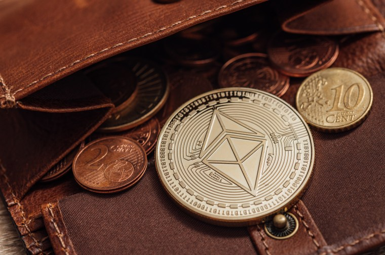 A commemorative coin bearing a double-pyramid logo lies in an open leather wallet containing euro coins