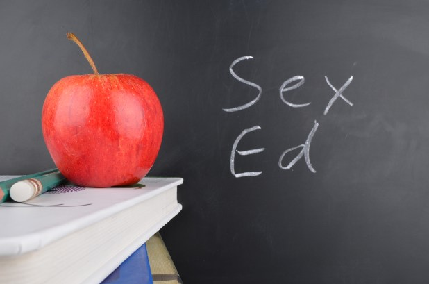 Apple and two pencils on pile of books next to blackboard that says 'Sex Ed'