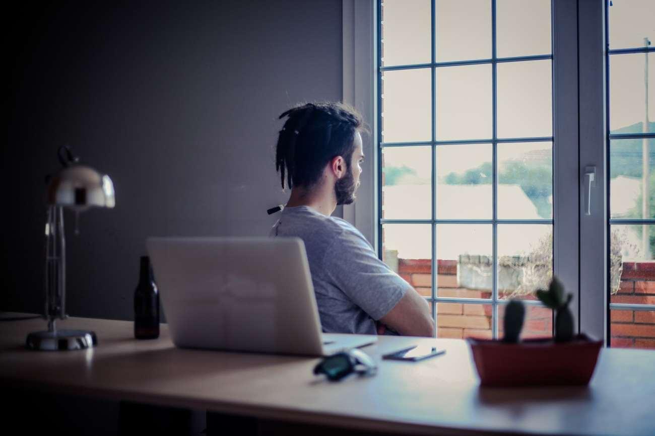 Uomo con le spalle alla scrivania, guardando fuori da una finestra.
