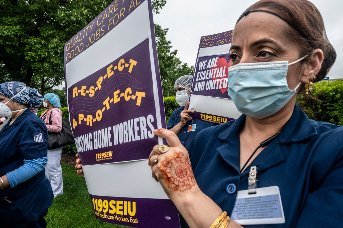 A nursing assistant with a badge holds a sign reading: Respect, Protect Nursing Home Workers