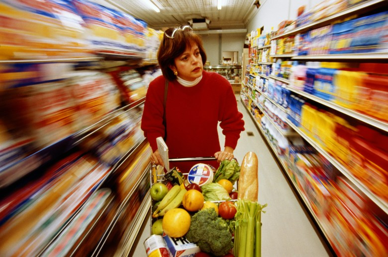 A stressed woman pushes a cart down a supermarket aisle.