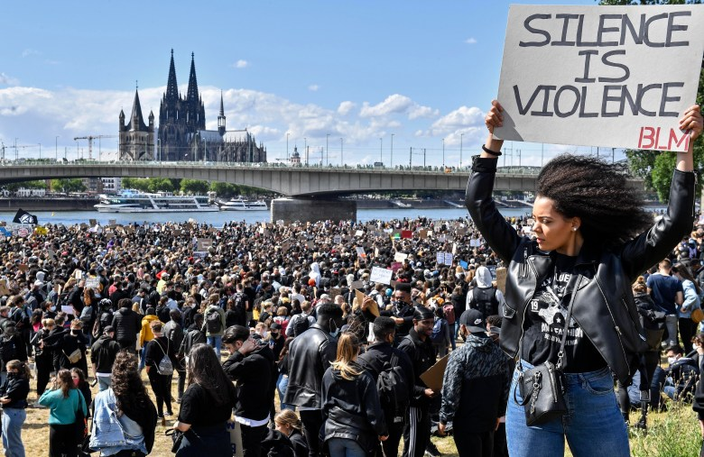 A woman holding a sign reading 'Silence is violence' and 'BLM' stands in front of a crowd