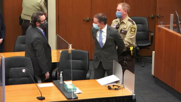 A sheriff's deputy handcuffs Derek Chauvin in the courtroom, while Chauvin speaks to his attorney