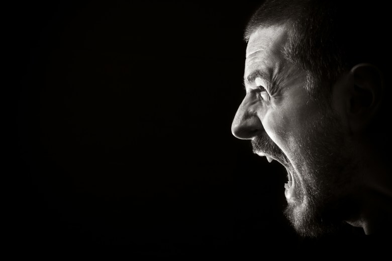 Perfil de hombre gritando.