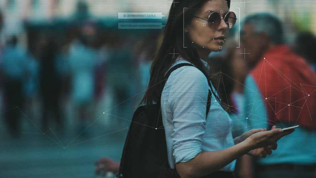 A woman holding a phone has facial recognition graphics around her face