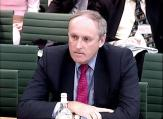 Paul Dacre sat in front of green chairs of parliamentary committee room.