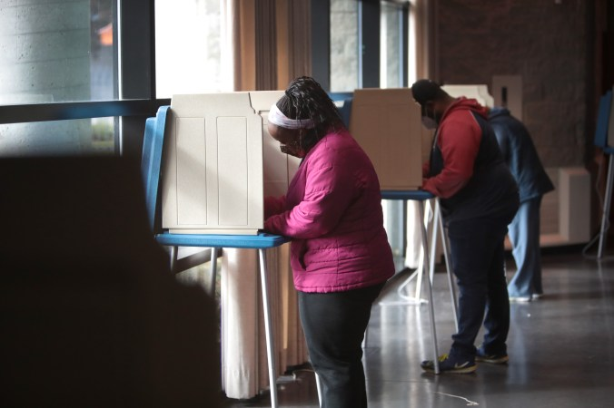Two people voting in a large public space.