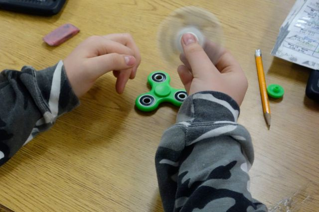 arms of a child wearing camo sweatshirt and holding a white fidget spinner at a school desk with pencil, eraser and green fidget spinner on desk in background