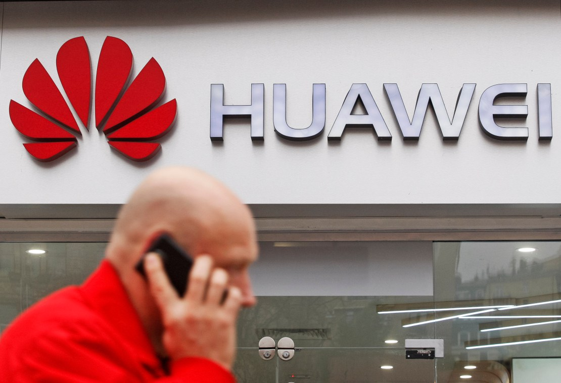 A man on the phone walking in front of a Huawei store