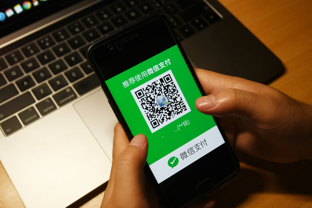 Someone holding a smartphone using the WeChat app to make a payment