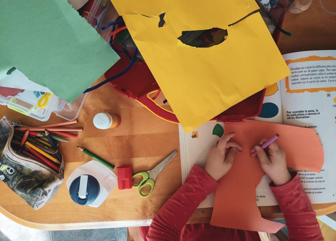 A child's hands are seen from above, working with glue and paper and scissors to make art