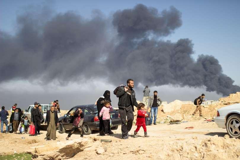 People walking carrying belongings with black smoke behind them.