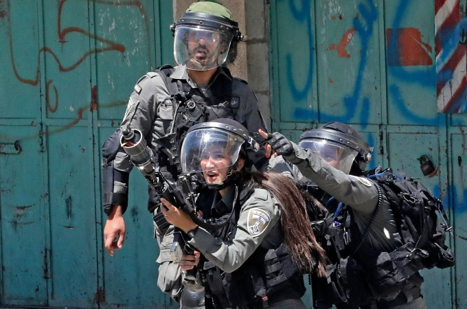 Three members of the Israeli security forces. One is firing tear gas.