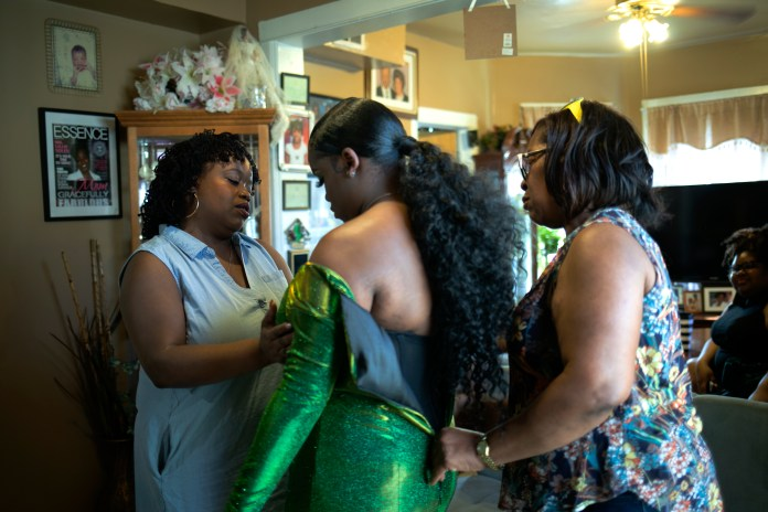 Two women help a young girl put on an emerald dress.
