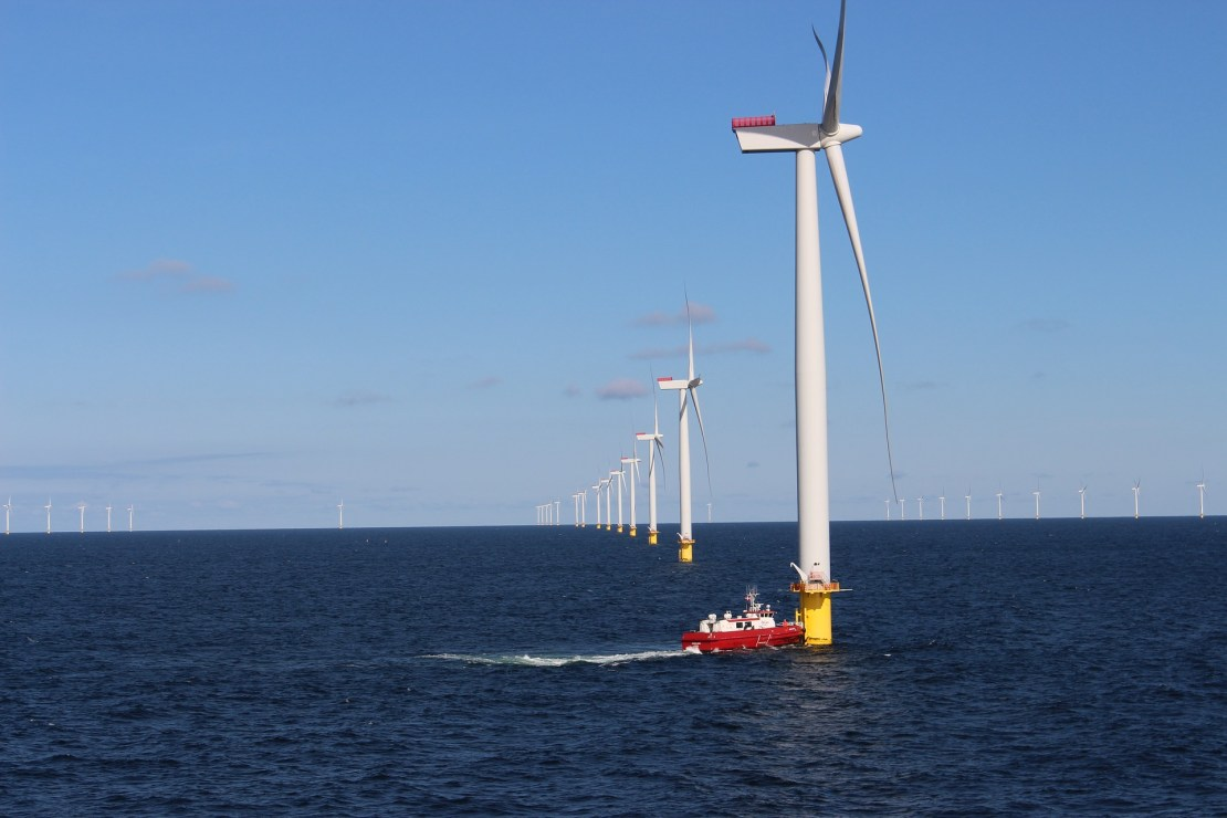 A red boat approaches a wind turbine at sea