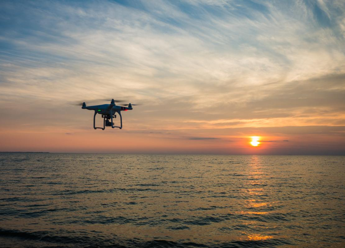 A drone is silhouetted against a sunset, with the sea beneath