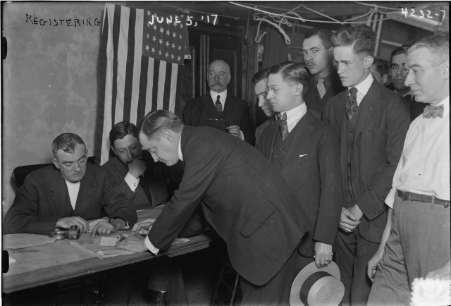 A group of men stand in line to fill out paperwork at a table staffed by other men