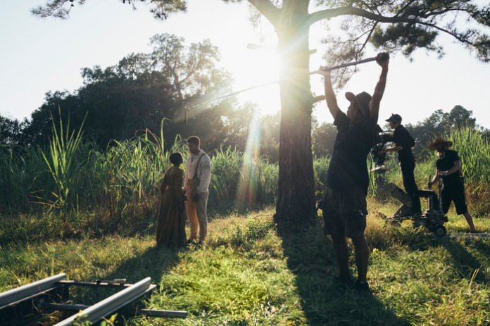 A set worker holds a boom in a sunny field while two actors act out a scene.