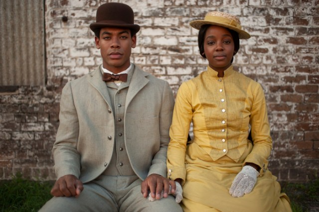 A man dressed in a dapper suit and hat poses, seated, next to a woman dressed in yellow.