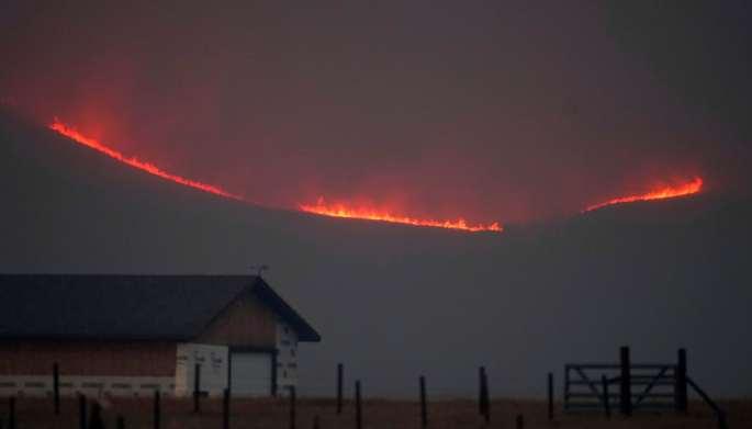Fire lights up a ridge behind a farm.