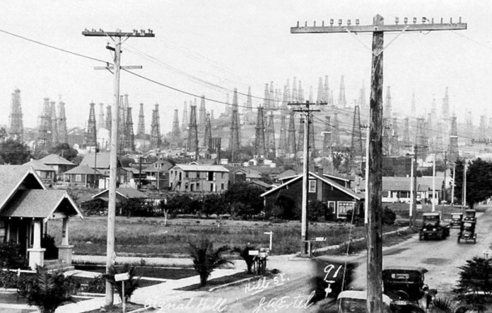 A historic black-and-white photo shows a street with houses, old cars and dozens of oil derricks on the hill behind them.