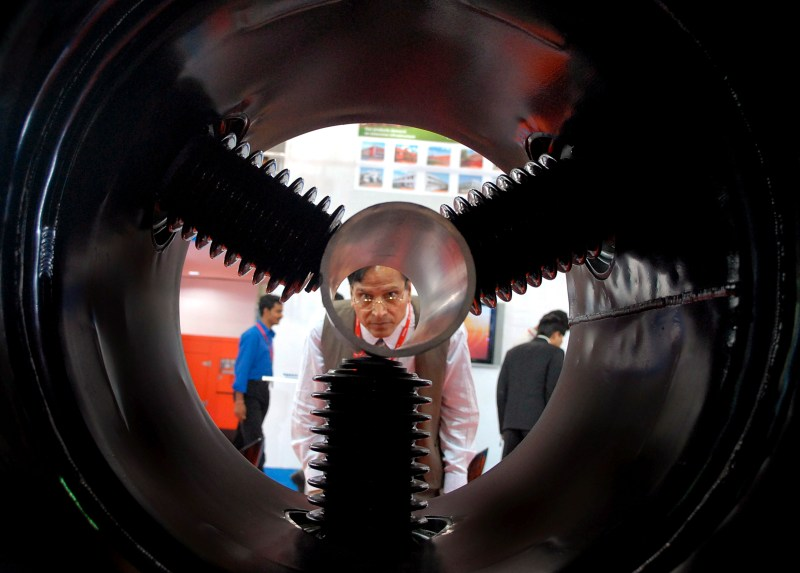 Man at exhibition in India looking at power plant component
