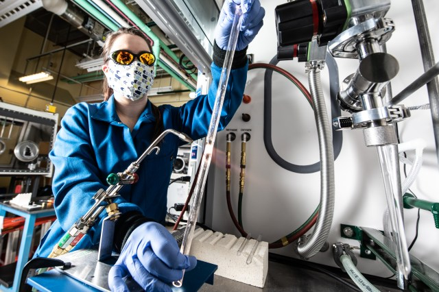 A woman works with a blow torch and glass tube