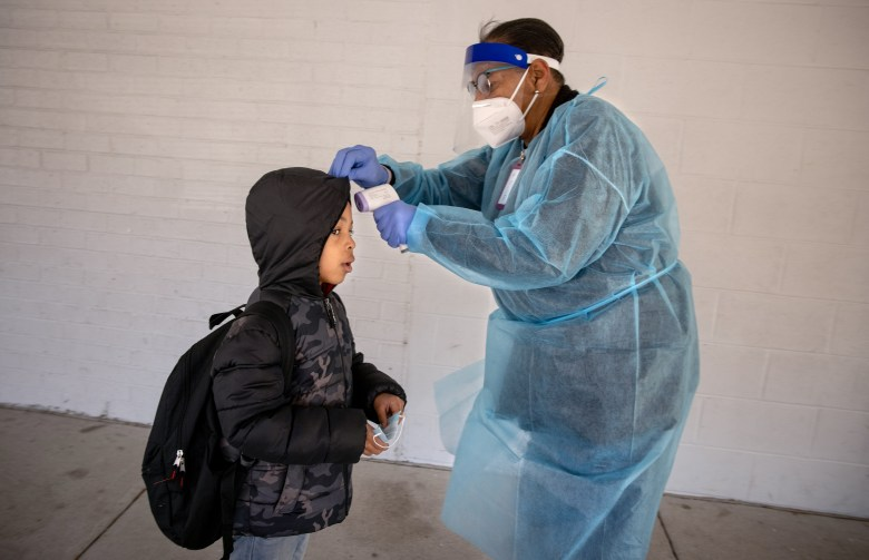 A school nurse takes a young student's temperature