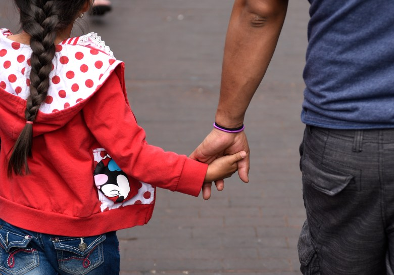 Father holds daughter's hand while walking together