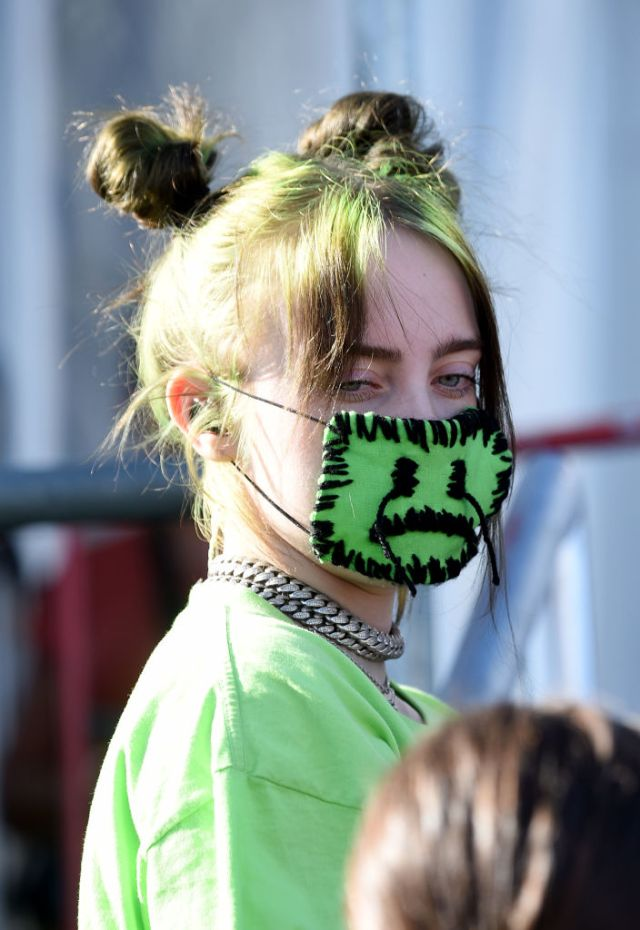 Billie Eilish wears a green mask with a sad face sewed into it.