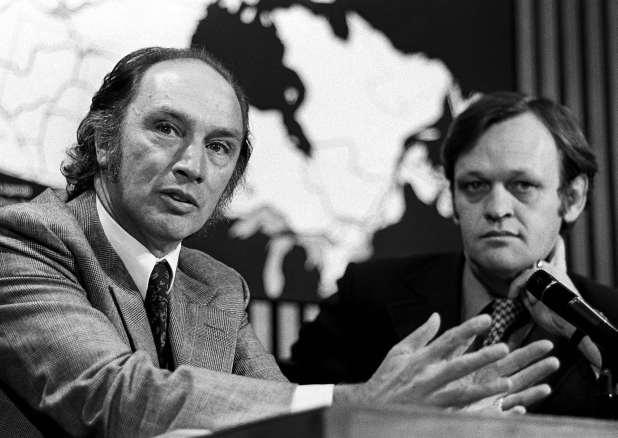 Pierre Trudeau speaks as Jean Chrétien sits beside him.