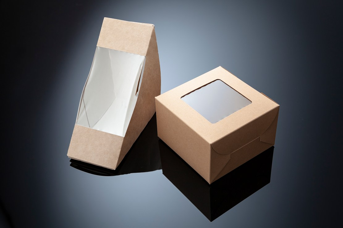 Two small cardboard boxes with plastic film inside them.