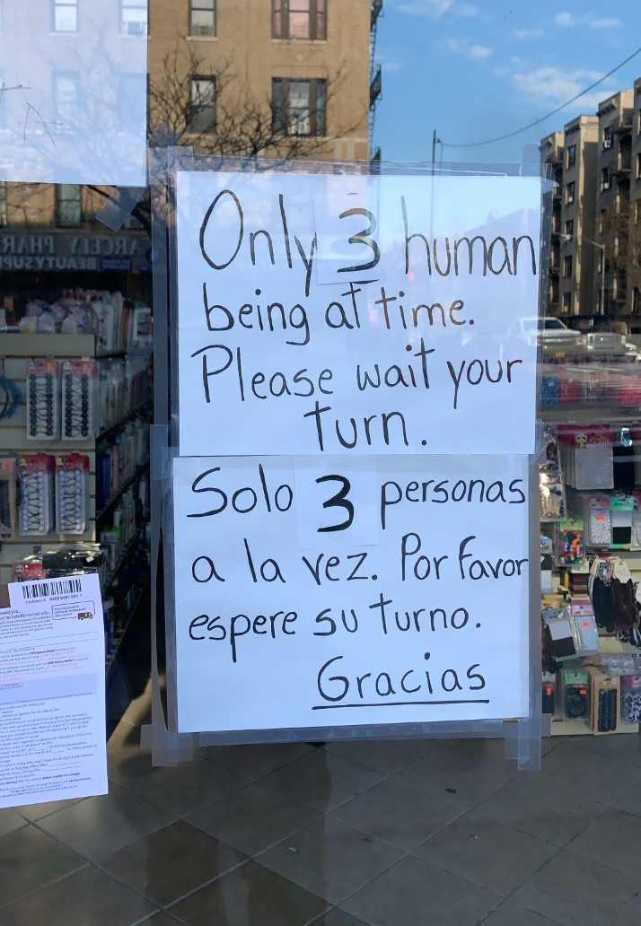 A sign in a storefront requests only three customers enter at a time.