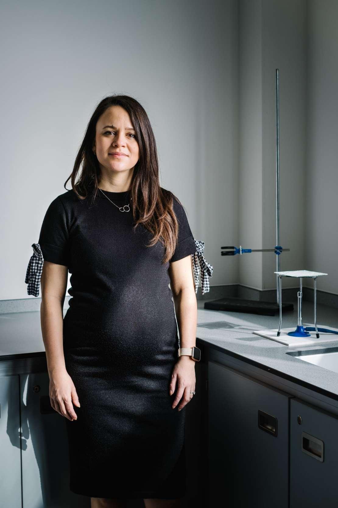School teacher standing in front of science equipment in class room