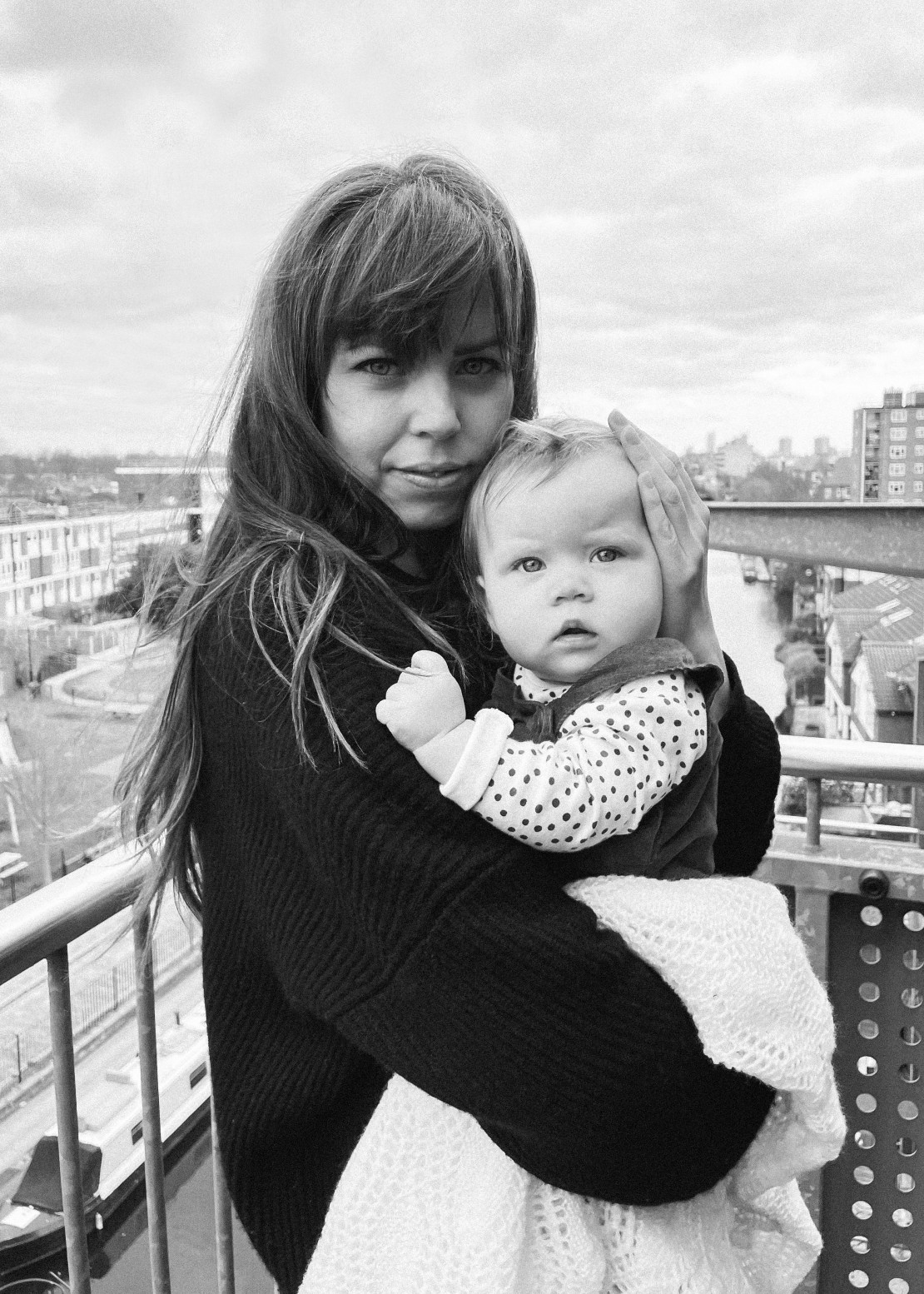 Woman holding her daughter on a balcony overlooking a canal