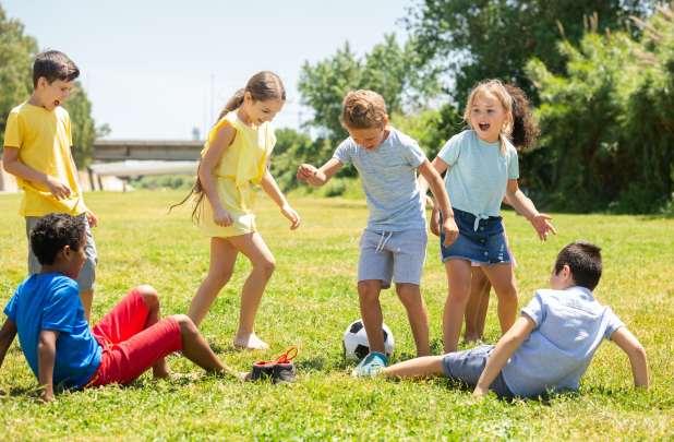 مجموعة من الأطفال يلعبون كرة القدم في الهواء الطلق في فصل الصيف.