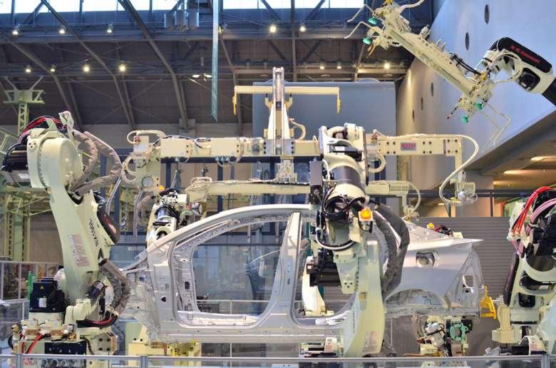Brazos robóticos en una fábrica ensamblan la carrocería de un coche.