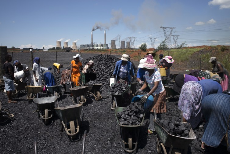 Women load coal from a pile on the ground into wheelbarrows.