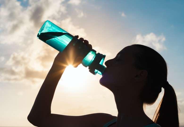 Mujer en contraluz bebiendo de un bote de agua.