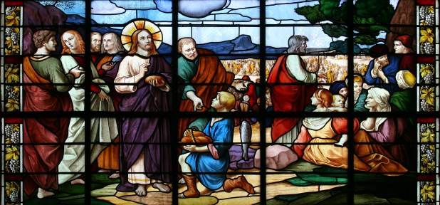 A stained-glass window depicting Jesus Christ feeding the 5,000.