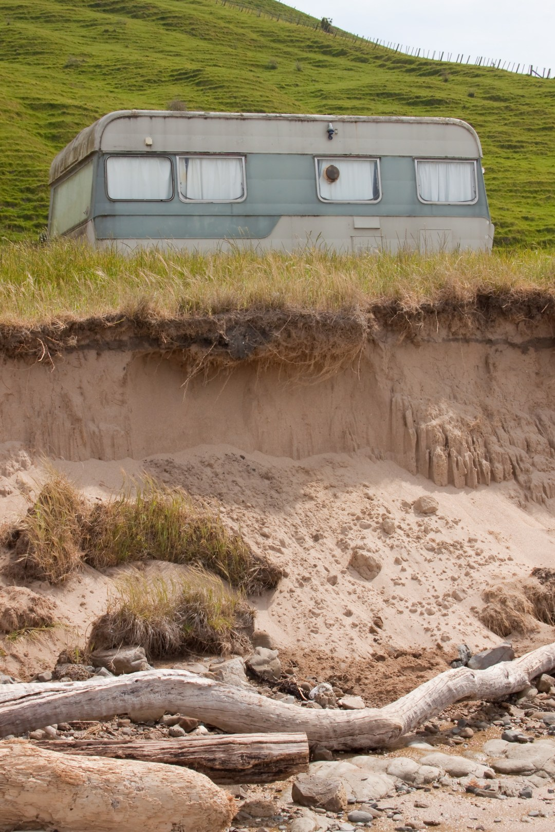 An eroded stretch of coast, with caravan parked.