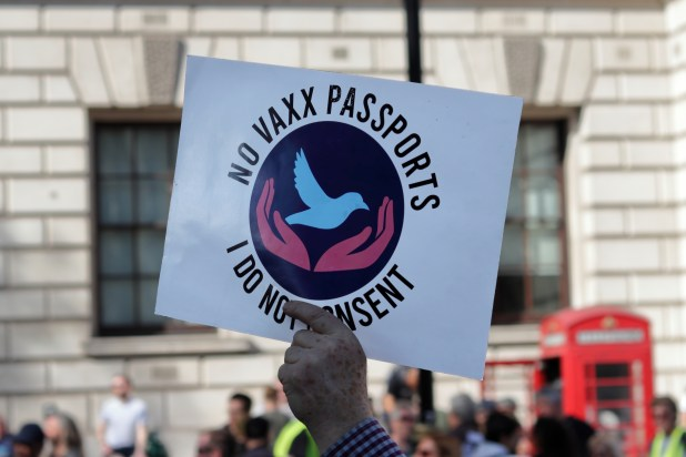 A person holding a sign saying 'No vaxx passports, I do not consent'