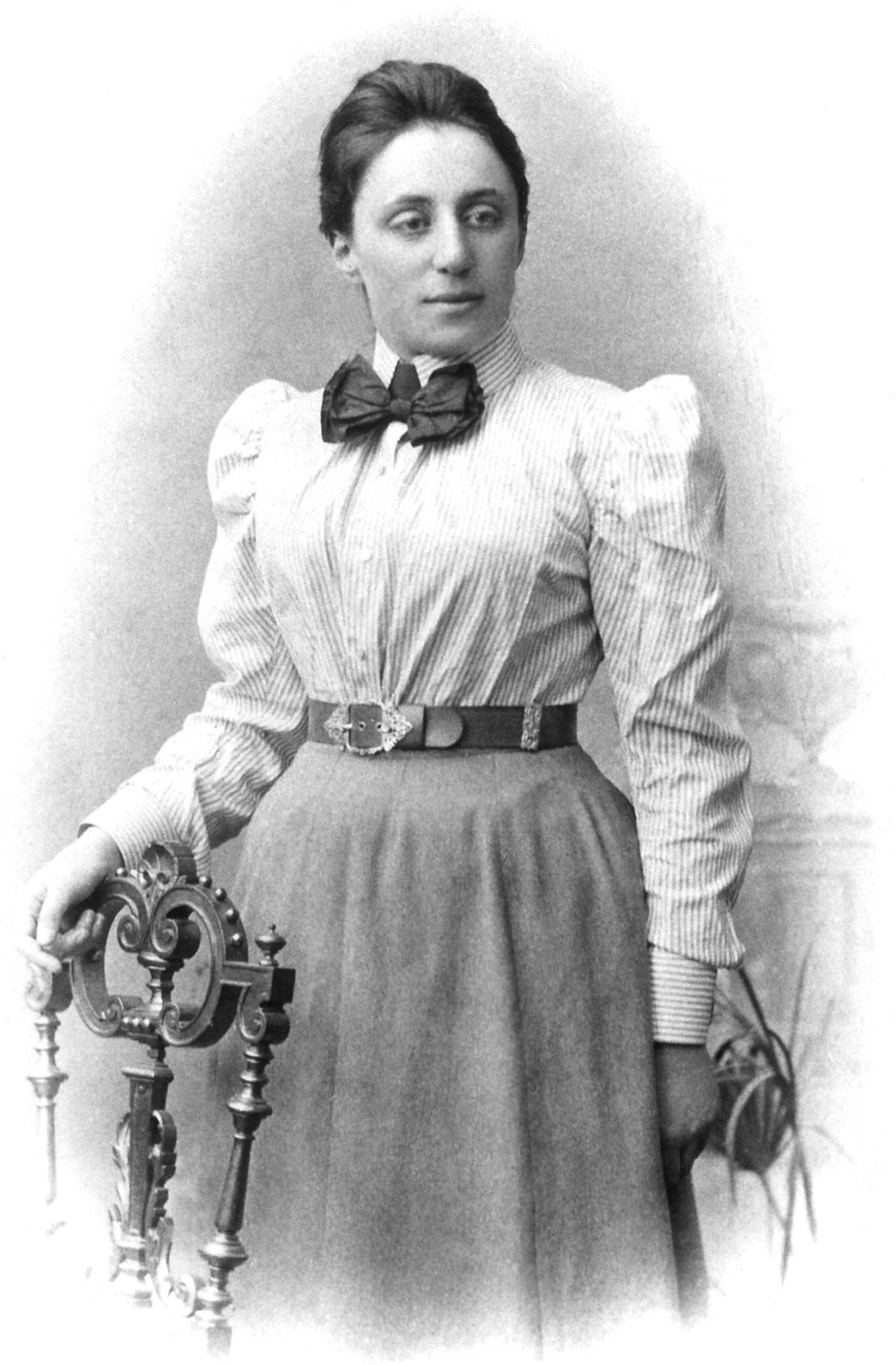 A black and white portrait of a young Emmy Noether in a shirt and a skirt.